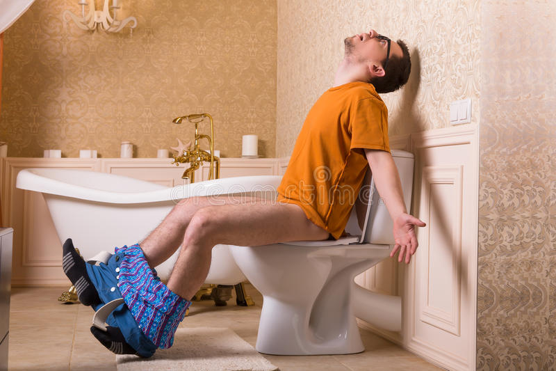 Mężczyzna z spodniami zestrzela obsiadanie na toaletowym pucharze zdjęcie royalty free