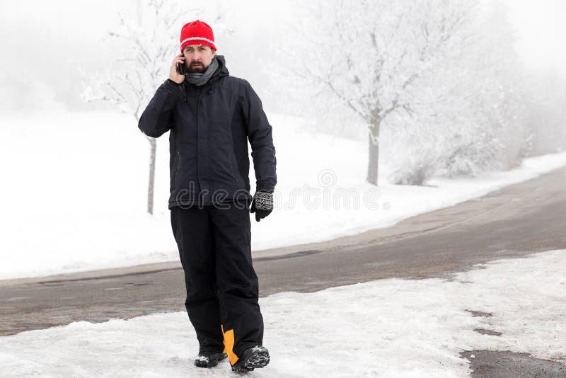 Mężczyzna z telefonem komórkowym chodzi przez lodowatą ulicę zdjęcie royalty free