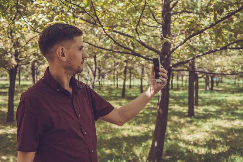 Mężczyzna z telefonem komórkowym w lato parku Młody przystojny mężczyzna z sm fotografia stock