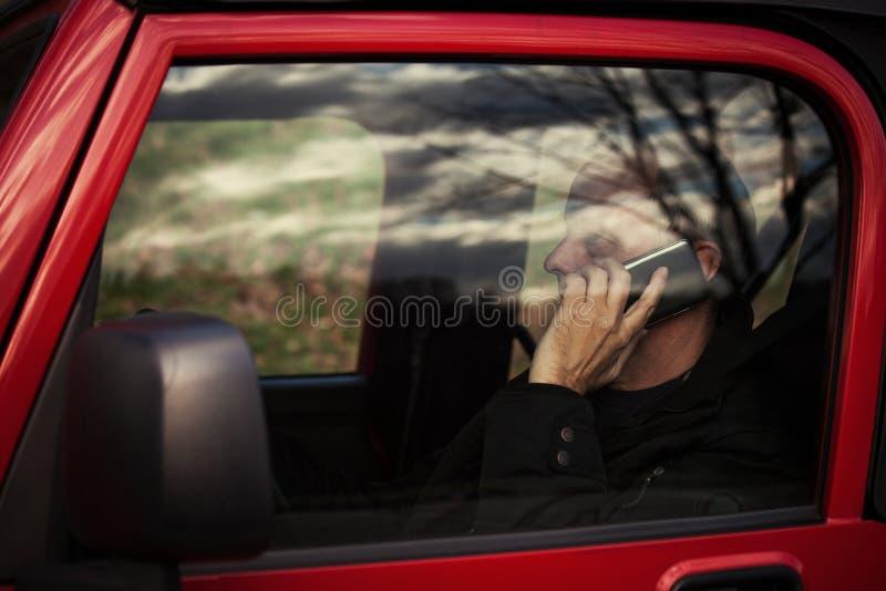 Mężczyzna z telefonem komórkowym w samochodzie obraz royalty free