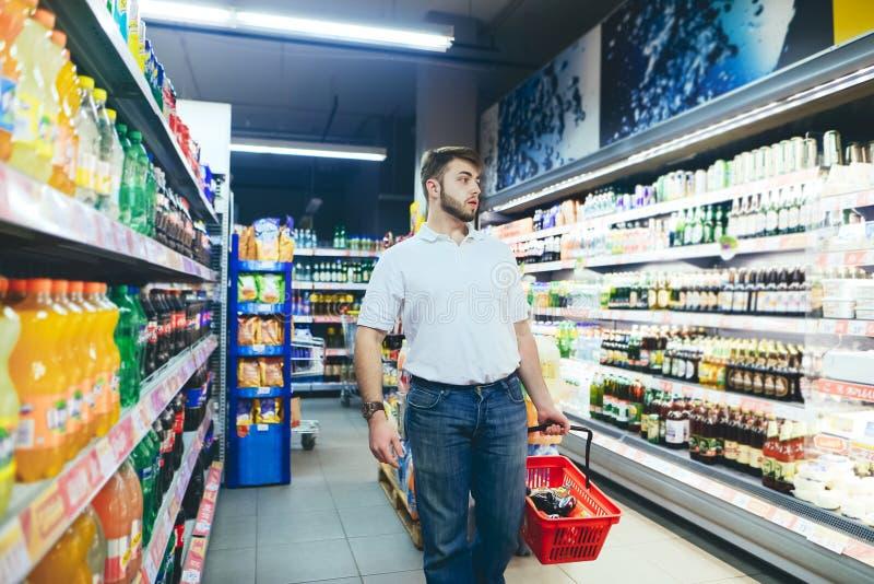 Mężczyzna z wózek na zakupy w jego rękach iść spojrzenia przy stronami i supermarket Nabywca wybiera produkty fotografia stock