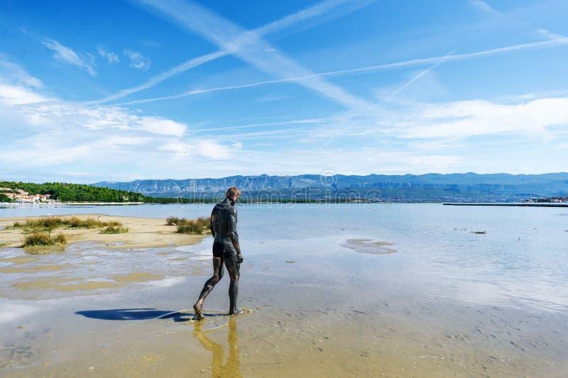 Mężczyzna zakrywający z leczniczym błotem chodzi na plaży zdjęcia royalty free