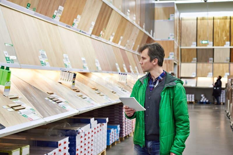 Mężczyzna zakupy laminat w DIY sklepie zdjęcia royalty free