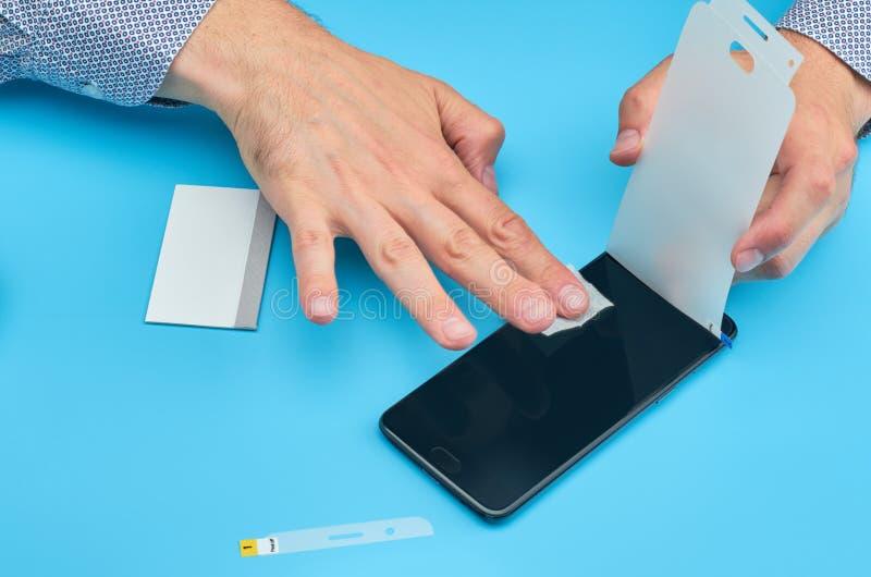 Mężczyzna zamienia łamającego hartownego szkło ekranu ochraniacza dla smartphone obrazy royalty free