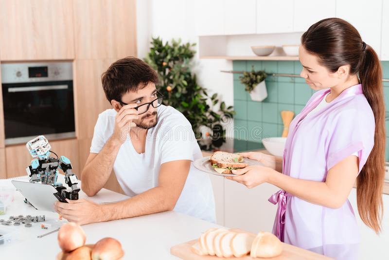 Mężczyzna zbiera robot w kuchni Dziewczyna przynosił on kanapkę Patrzeje ona z jego szkłami zestrzela zdjęcie royalty free