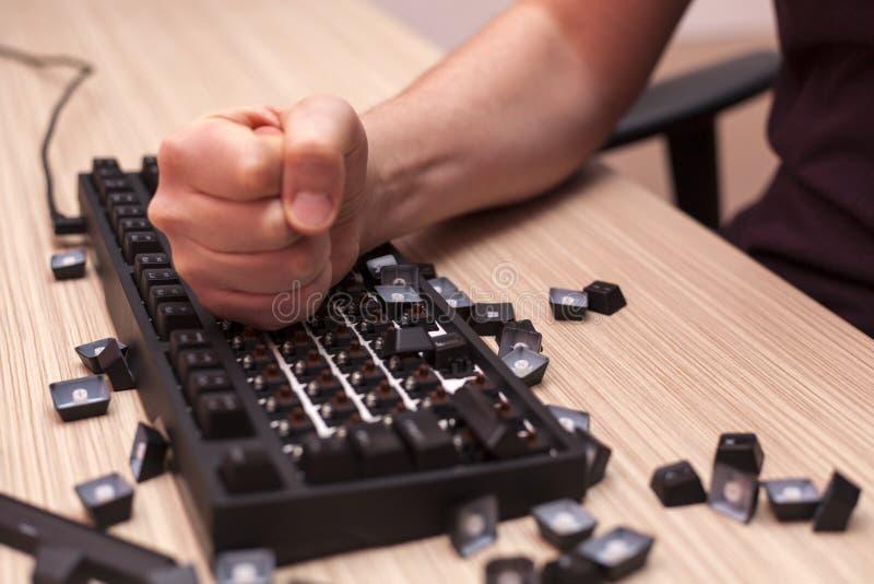 Mężczyzna zdecydowanie niszczy machinalną komputerową klawiaturę w furii używać jeden pięść obraz royalty free