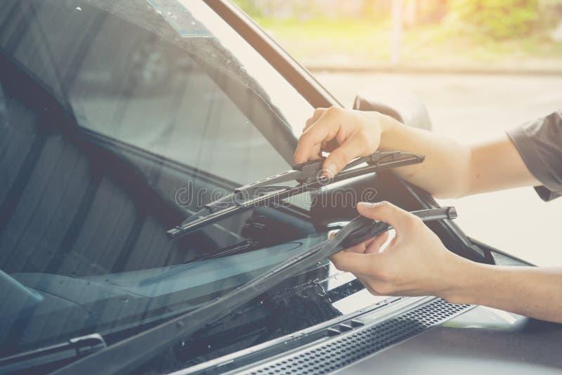 Mężczyzna zmienia windscreen wipers na samochodzie obrazy royalty free