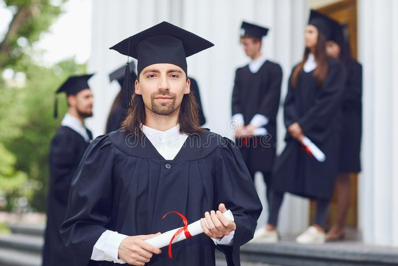 Mężczyzny absolwent jest uśmiechnięty przeciw tłu uniwersyteccy absolwenci zdjęcia royalty free