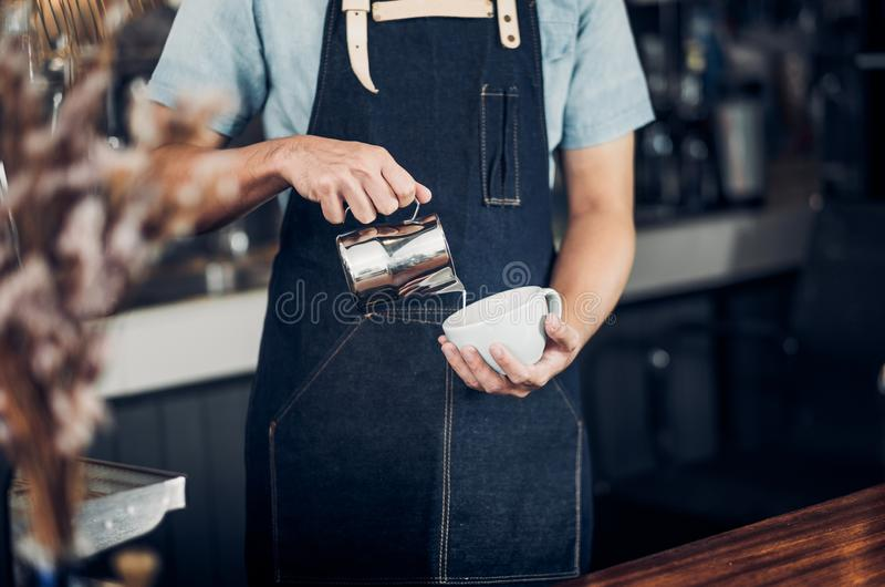 Mężczyzny barista nalewa mleko w gorącą filiżankę przy kontuaru barem przed maszyną w cukiernianej restauracji, Karmowy właścicie obrazy royalty free