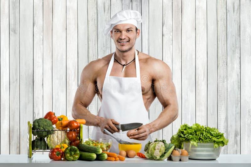 Mężczyzny bodybuilder kucharstwo na kuchni obraz stock