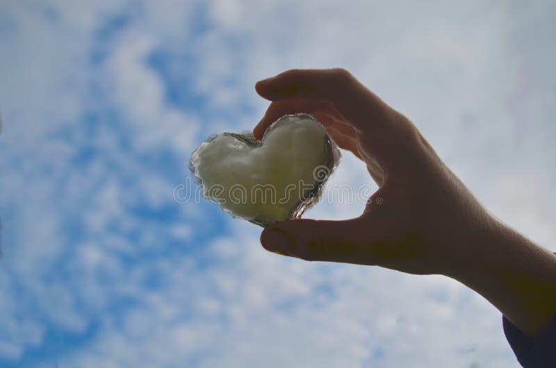 Mężczyzny chwyta ręka do nieba w formie miłości serca z sercem na natury światła słonecznego chmurze i racy zdjęcie stock