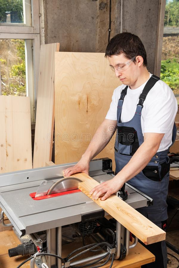 Mężczyzny cieśla piłuje drewnianą deskę na woodworking maszynie zdjęcia royalty free