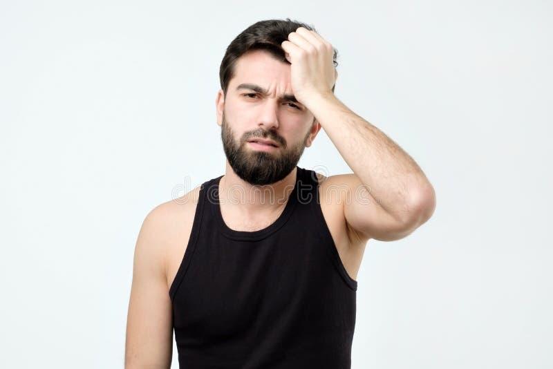 Mężczyzny cierpienie od migreny próbuje uśmierzać ból z bezradnym wyrażeniem obraz stock