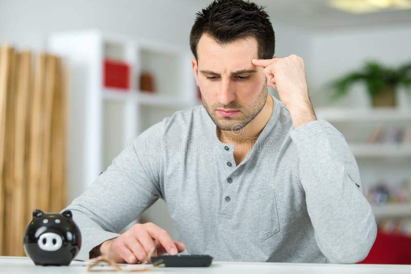 Mężczyzny cyrklowania pracujący finanse z prosiątko bankiem na stole obrazy stock