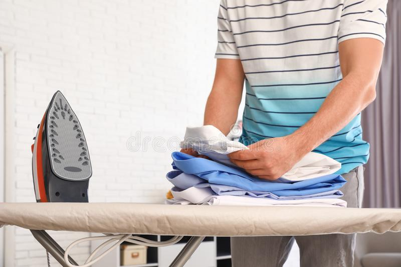 Mężczyzny falcowanie odziewa na prasowanie desce w domu zdjęcia stock