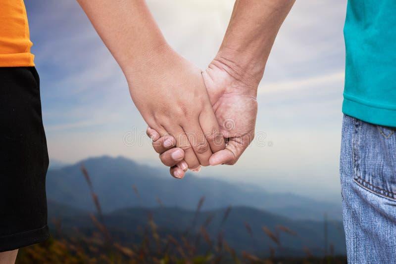 Mężczyzny i kobiety mienia ręka na zamazanym natury tle zdjęcia royalty free