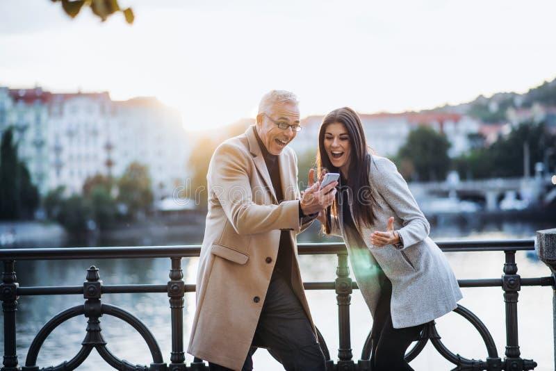 Mężczyzny i kobiety partnery biznesowi z smartphone pozycją w mieście, wyraża podniecenie obrazy stock