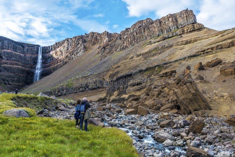 Mężczyzny i kobiety turyści cieszy się spektakularny krajobraz wokoło basaltic warstwy z cienkim, czerwienią i kolorem żółtym, zdjęcie royalty free
