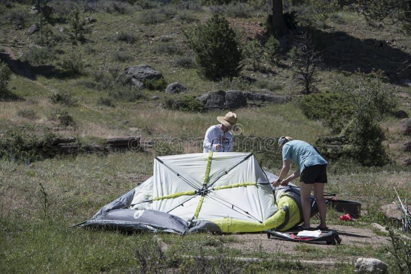 Mężczyzny i kobiety utworzenie namiot w obozowisku dla nocnego campingu obraz royalty free