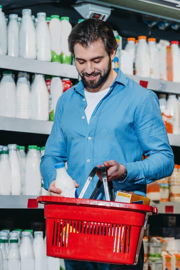 mężczyzny kładzenia butelka mleko w zakupy kosz obrazy royalty free