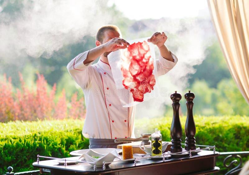 Mężczyzny kucharz ciie mięso z nożem w restauracji obrazy stock