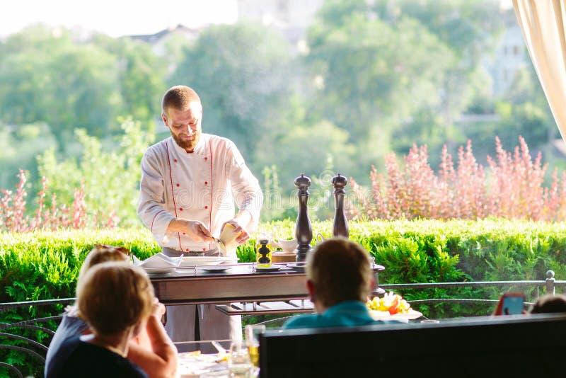 Mężczyzny kucharz ciie mięso z nożem w restauracji zdjęcie royalty free
