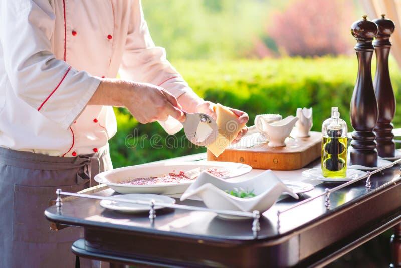 Mężczyzny kucharz ciie mięso z nożem w restauracji zdjęcia royalty free