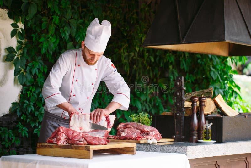 Mężczyzny kucharz ciie mięso z nożem w restauracji zdjęcie stock