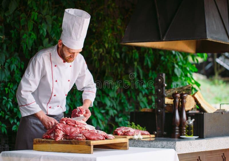 Mężczyzny kucharz ciie mięso z nożem w restauracji obrazy royalty free