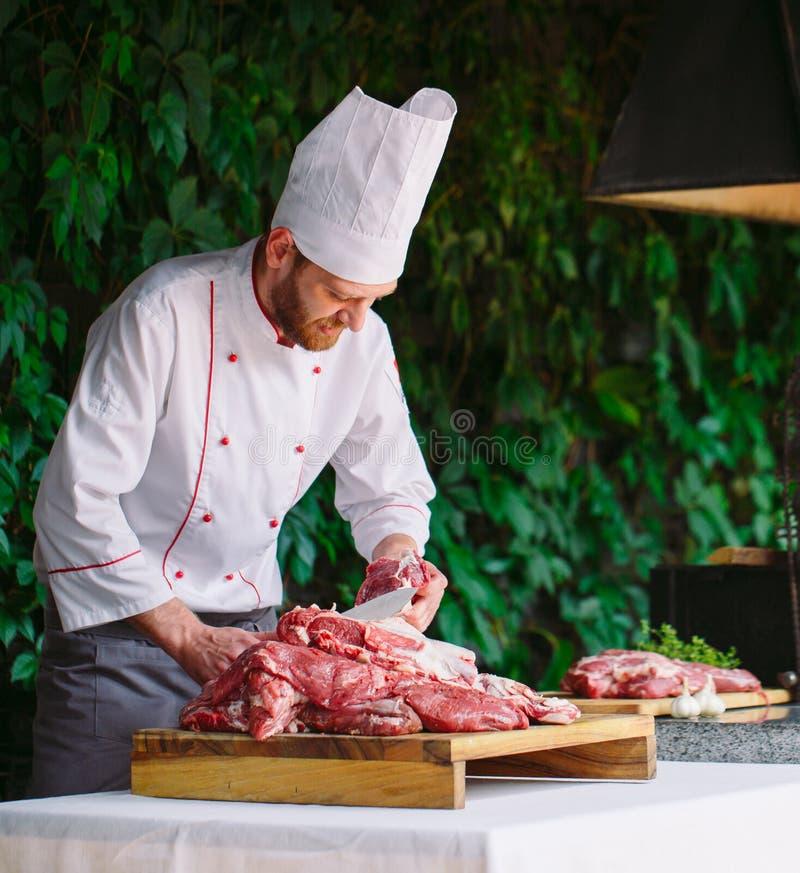 Mężczyzny kucharz ciie mięso z nożem w restauracji obraz stock
