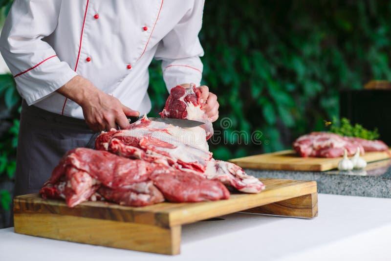 Mężczyzny kucharz ciie mięso z nożem w restauracji zdjęcia stock