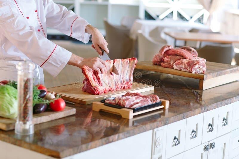 Mężczyzny kucharz ciie mięso z nożem w restauracji fotografia royalty free