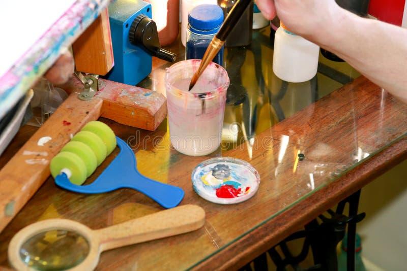 Mężczyzny malarz miesza kolory zanim malujący przy sztuki farby studiiem Artysta w jego ręki mienia paintbrush mieszał kolor nafc zdjęcia stock