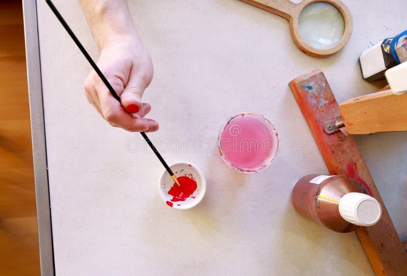 Mężczyzny malarz miesza kolory zanim malujący przy sztuki farby studiiem Artysta w jego ręki mienia paintbrush mieszał kolor nafc obraz stock