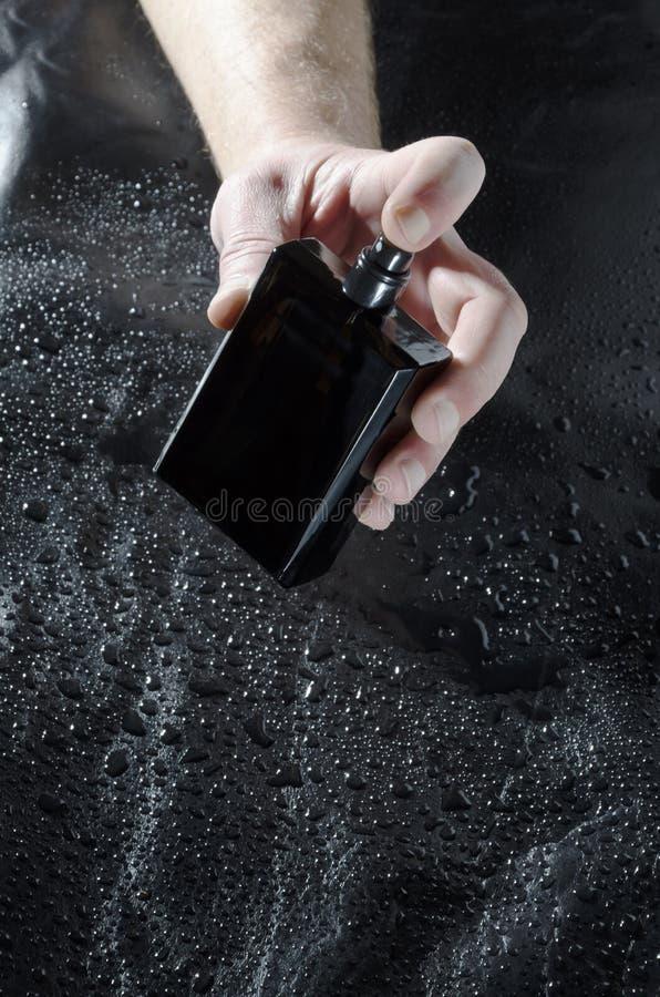 Mężczyzny mienia butelka woń przeciw wodnym kroplom na skóry powierzchni obraz royalty free