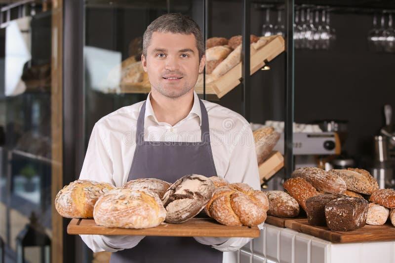 Mężczyzny mienia deska z asortymentem świeży chleb w piekarni obraz royalty free
