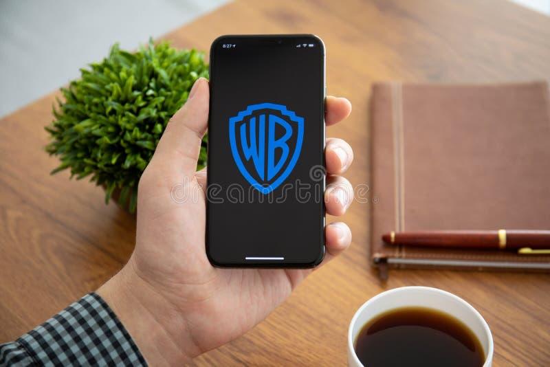 Mężczyzny mienia iPhone X z firmą Warner Bros Lać się wideo obraz royalty free