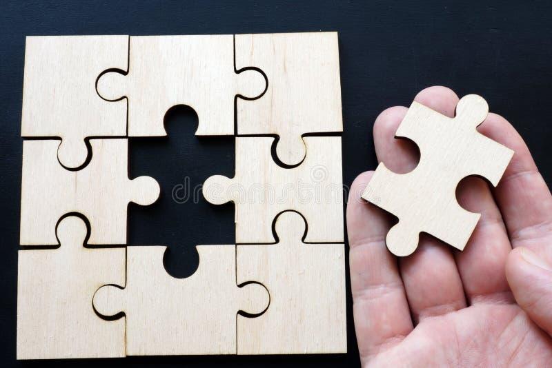 Mężczyzny mienia kawałek łamigłówka Rozwiązanie problem z biznesem zdjęcia stock