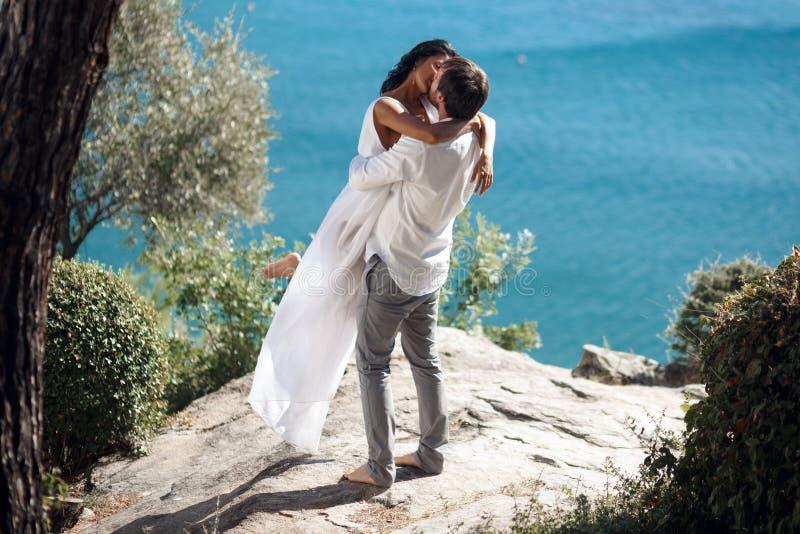 Mężczyzny mienia kobieta w jego rękach zawijać wokoło jej jej i talii trzyma dalej on, stojący blisko morza w Grecja zdjęcie royalty free