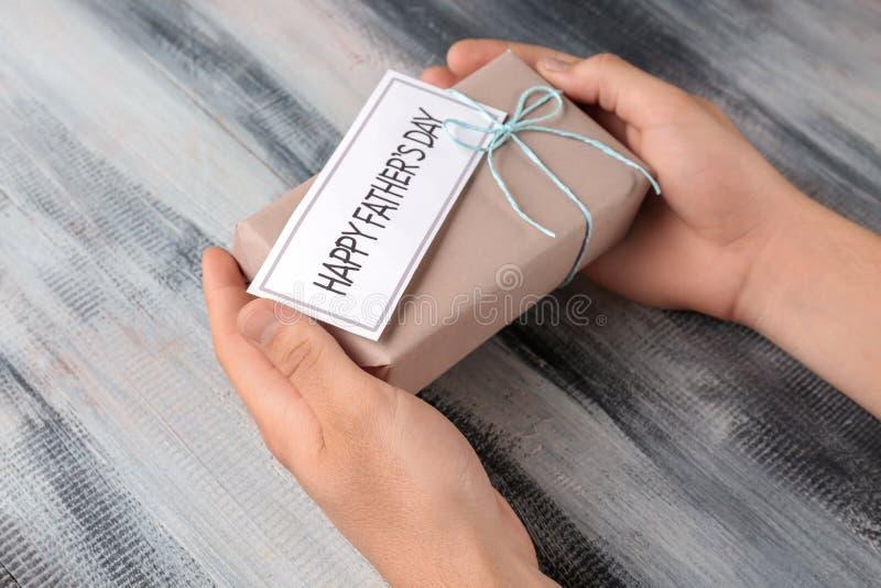 Mężczyzny mienia prezenta pudełko z SZCZĘŚLIWĄ ojca dnia kartą na drewnianym tle zdjęcie royalty free