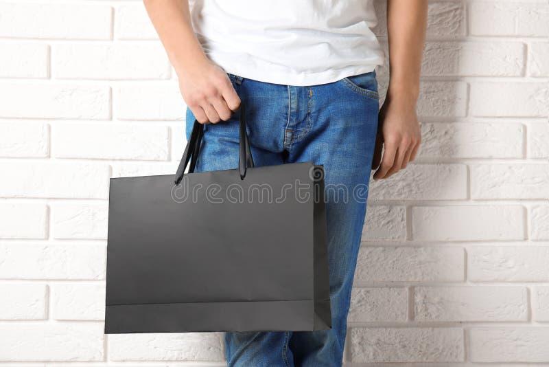 Mężczyzny mienie w górę papierowej torby na zakupy ściany obrazy royalty free