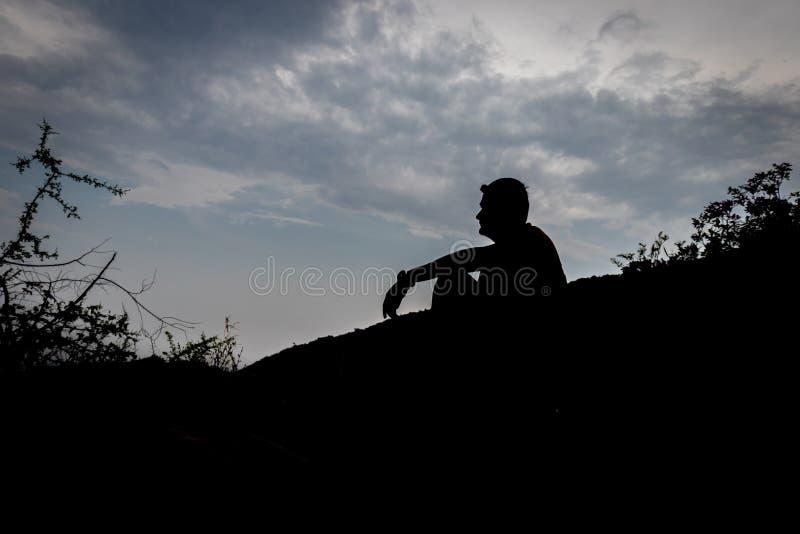 Mężczyzny obsiadania cień z niebieskiego nieba tłem stan samotność zdjęcie stock