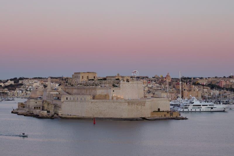 Mężczyzny obsiadanie na ławce i patrzeć fortu St w Vittoriosa Angelo i Uroczysty schronienie, Malta zdjęcia royalty free