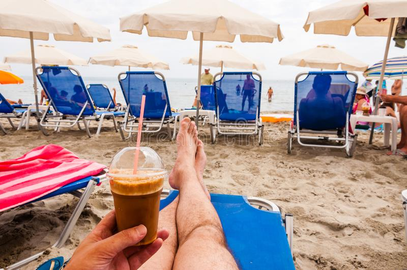 Mężczyzny obsiadanie na błękitnym deckchair z lodową kawą w ręce na Paralia plaży na morza egejskiego wybrzeżu w Grecja zdjęcie stock