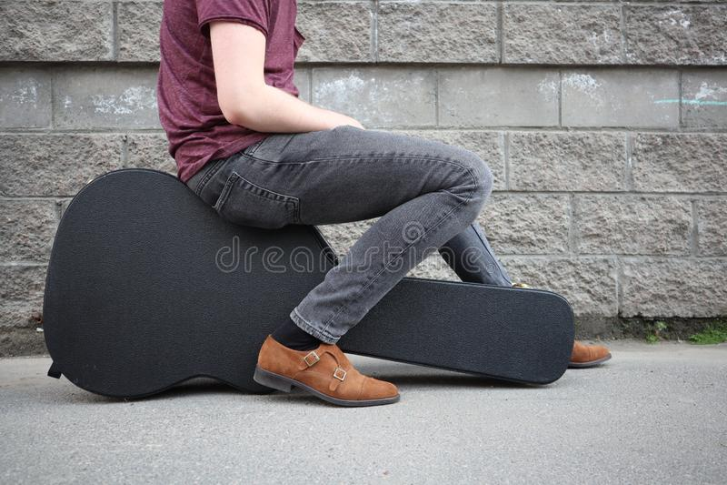 Mężczyzny obsiadanie na czarnej gitary skrzynce Ci??ka skrzynka dla gitary elektrycznej fotografia stock