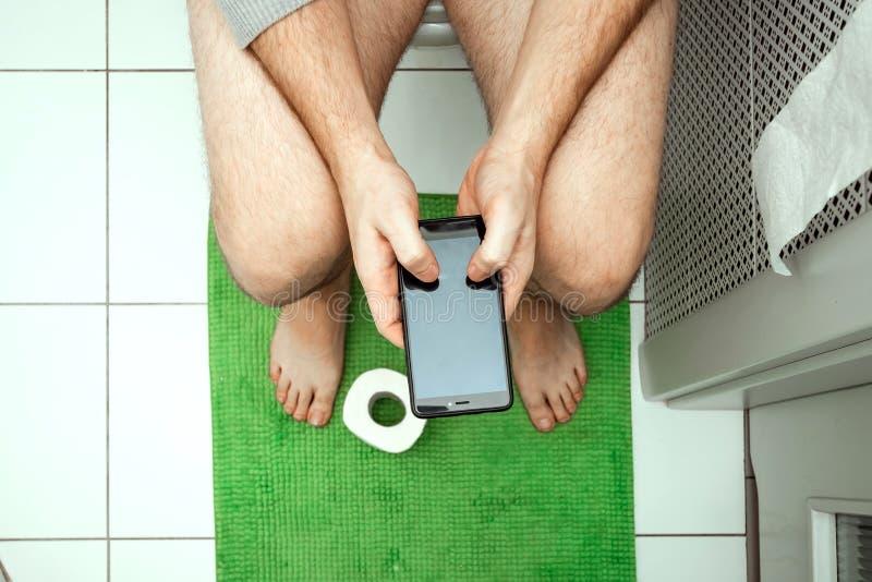 Mężczyzny obsiadanie na toaletowym mieniu smartphone w jego rękach, odgórny widok Pojęcie problemy z krzesłem, jelita, obrazy stock