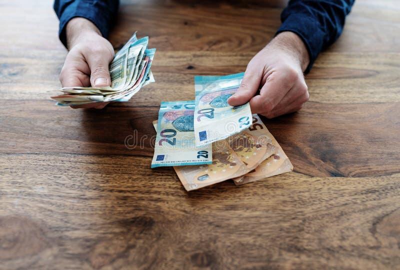Mężczyzny obsiadanie przy biurko odliczającym pieniądze zdjęcie stock