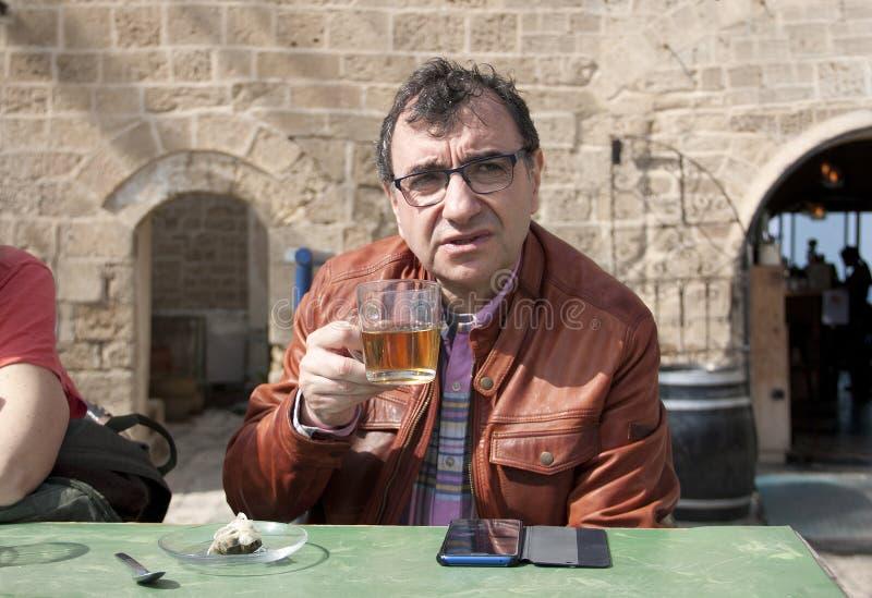 Mężczyzny obsiadanie w kawiarni z filiżanką herbata fotografia royalty free