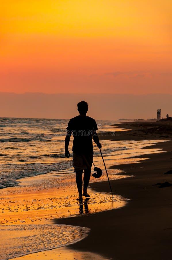 Mężczyzny odprowadzenie w plaży przy zmierzchem z jego kijem i kapeluszem kolorowe t?o fotografia stock
