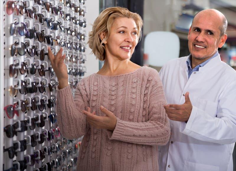 mężczyzny okulisty klient doradza Dojrzałej blondynki blisko pokazów okularów przeciwsłonecznych obraz royalty free